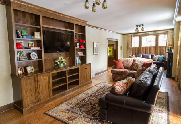 Living room with leather couch and large wooden bookcase