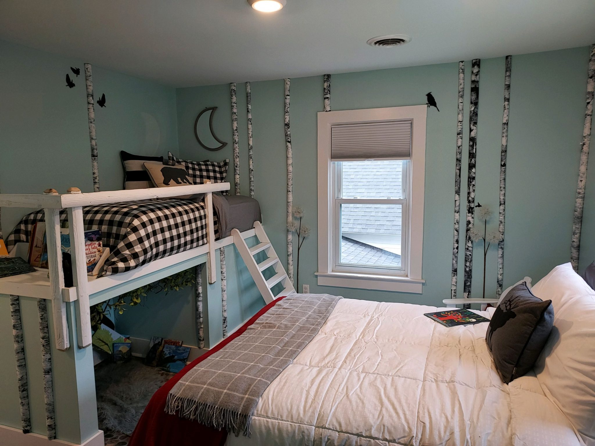 A bedroom at the Ronald McDonald Family Retreat at Krantz Cottage, featuring faux birch branches and other Adirondack decor.