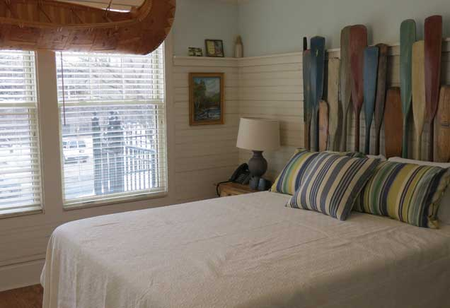 Queen bed with white bedding in room with canoe-themed decor
