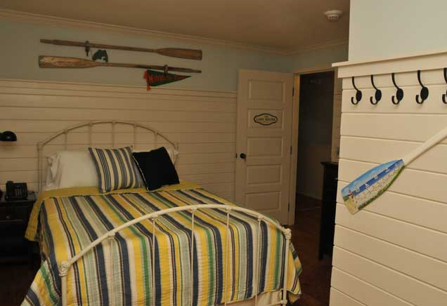 Queen bed with blue, green, and yellow striped bedding in room with canoe-themed decor
