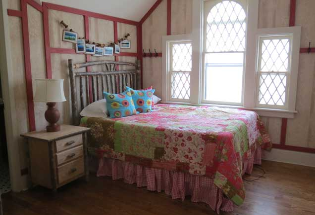 Queen bed with pink patchwork bedding in an Adirondack-themed room