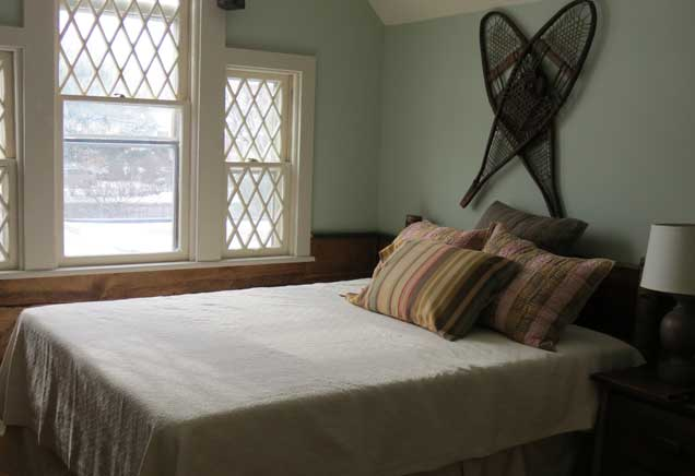 Queen bed with white bedding in an Adirondack-themed room