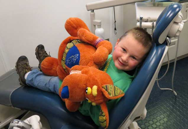 Boy with large stuffed animal smiles in dentist's chair