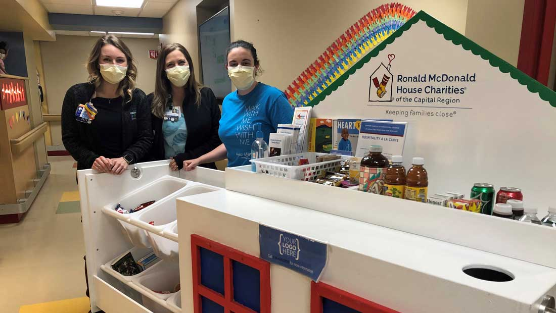 Three hospital workers stand wearing face masks with the RMHC-CR Hospitality Cart
