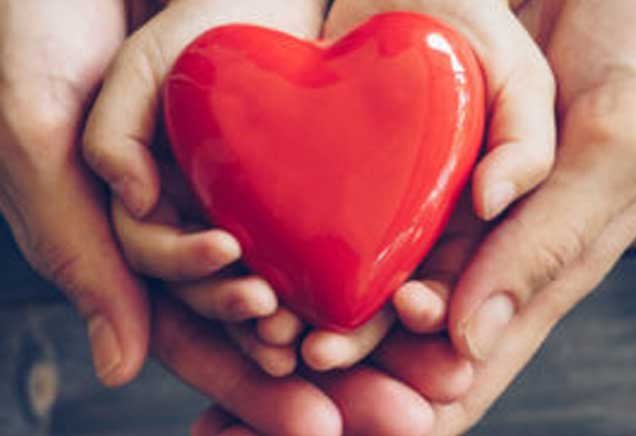Red heart in child's hands surrounded by adult hands