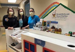Three female hospital workers pose with the RMHC Hospitality Cart at Albany Med during COVID-19
