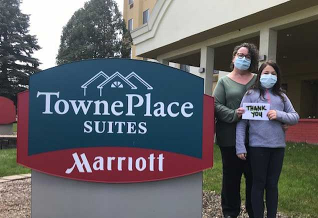 Mother and daughter stand outside of TownePlace Suites by Marriott holding thank you sign