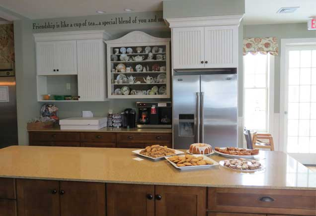 Kitchen island with tan marble countertops and baked goods on display