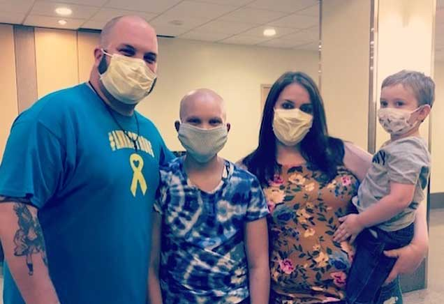 Family of four poses for a picture while wearing face masks