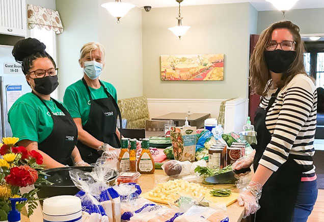 Volunteers wearing masks and gloves stand around a kitchen island preparing dinner at the Ronald McDonald House