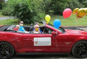 Grand marshals sit in a red convertible with balloons to lead RMHC parade