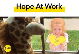 "Child seen through window holding ""Hope Lives Here"" yellow heart"