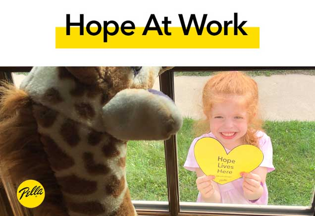 """Child seen through window holding """"Hope Lives Here"""" yellow heart"""
