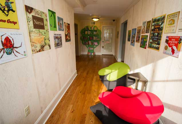 Play area decorated with children's books and colorful bean bags
