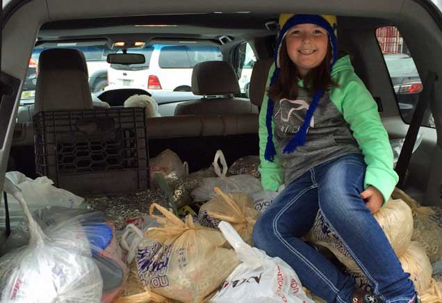 Young girl sits in the back of a car filled with bags of pull tabs