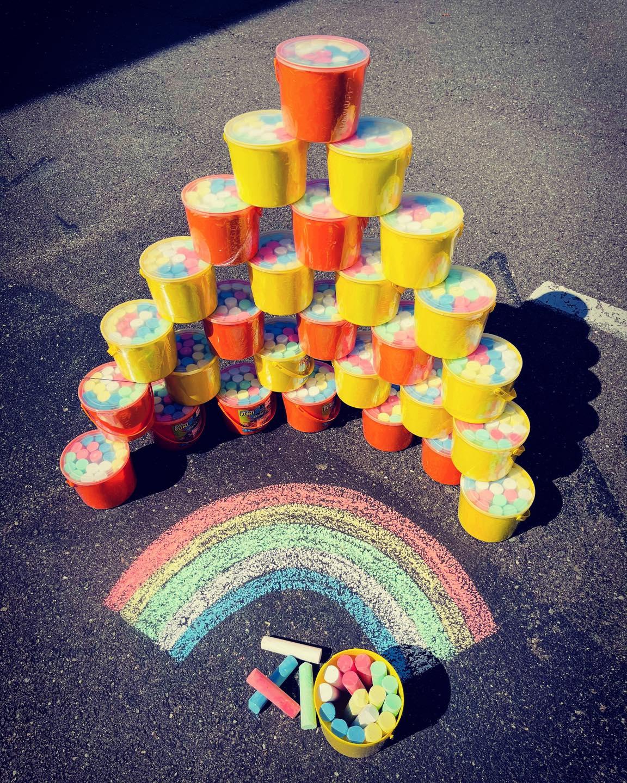 Buckets of chalk stacked around chalk rainbow