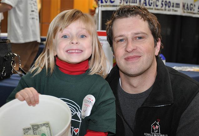 Chad O'Hara with smiling child at RMHC Radiothon