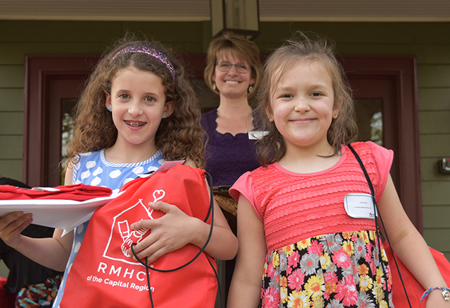 Two young girls smiling with prizes from the READ for RMHC-CR program