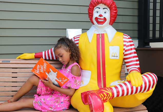 Young girl sits on bench with book next to Ronald McDonald statue