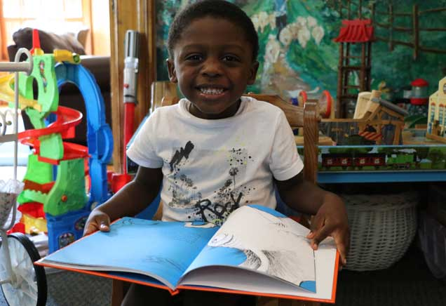 Boy smiles with big book in hands
