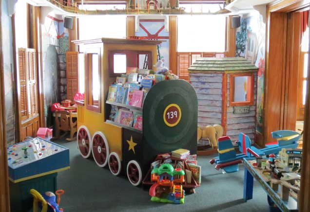 Child's playroom filled with toys, books and a train