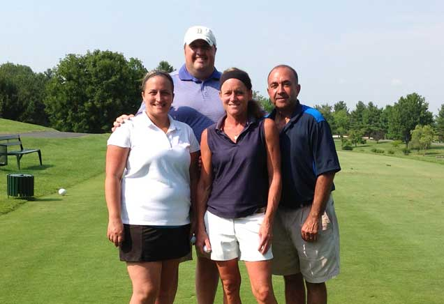 A foursome of two men and two women stand together on a golf course