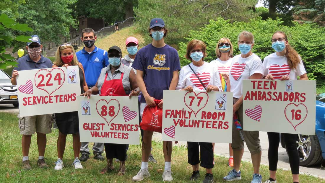 Large group of RMHC volunteers posing with face masks and posters