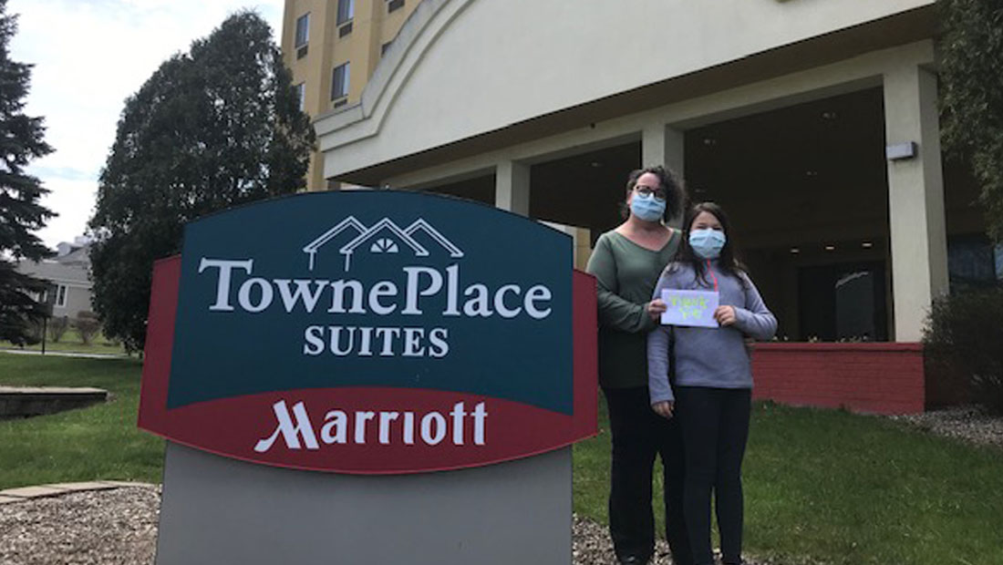 Mother and daughter stand in front of hotel with thank you sign