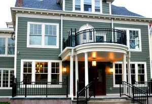 Green Victorian house with black porch railing and porch lights on